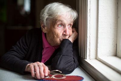 Adulta mayor viendo por la ventana